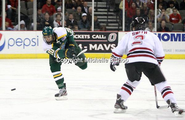 Alaska-Anchorage's Alex Gellert shoots the puck as Nebraska-Omaha's Matt Smith defends. (Photo by Michelle Bishop) .