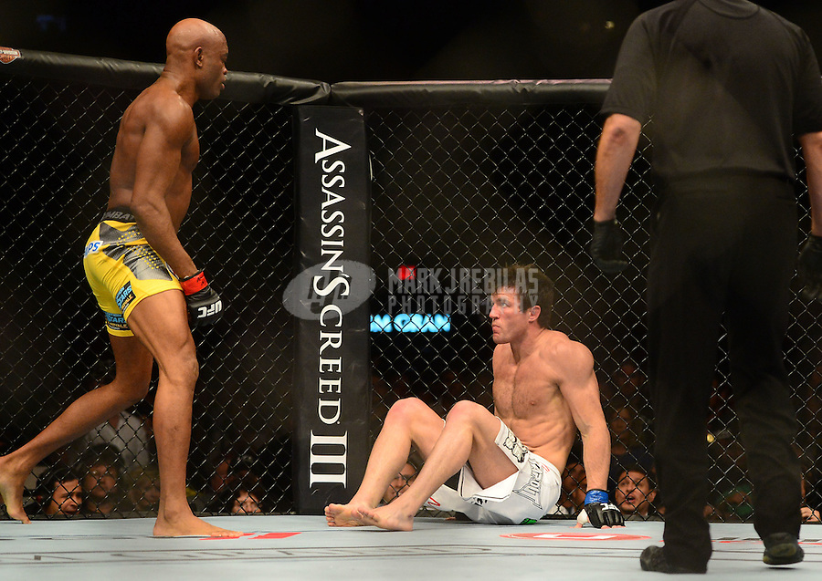 Jul. 7, 2012; Las Vegas, NV, USA; UFC fighter Anderson Silva (left) looks at Chael Sonnen on the ground during a middleweight bout in UFC 148 at the MGM Grand Garden Arena. Mandatory Credit: Mark J. Rebilas-