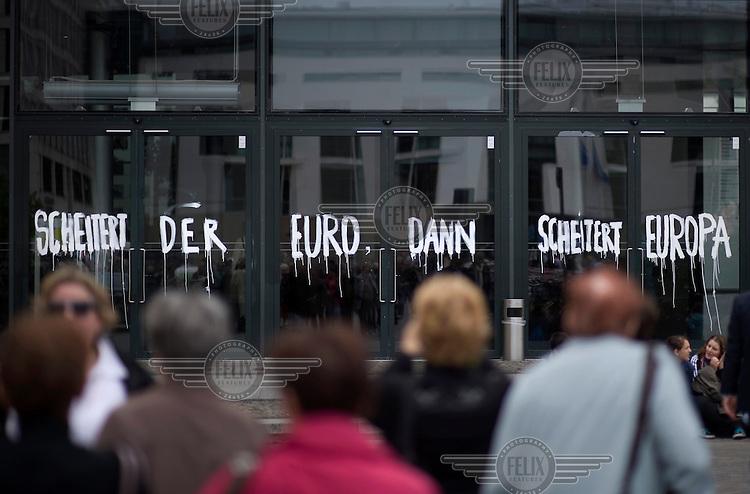 People pass Grafitti, part of an art work showing in the 7. Berlin Biennale for Contemporary Art at the Akademie der Kuenste, that reads: 'SCHEITERT DER EURO SCHEITERT EUROPA'.