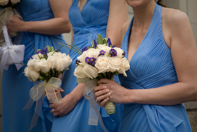 Close-up of bridesmaids in blue dresses holding bouquets.