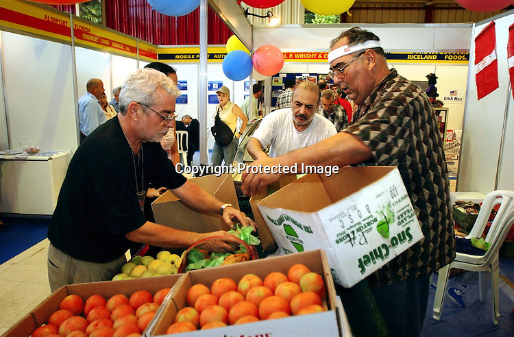 Cuba Trip.Scanned 11/21/2003.Erik Kellar/Staff..FRUITS OF NEGOTIATION.Michael R. Mauricio, president of Florida Produce in Tampa, left, unpacks his shipment of display fruit with Rex Rodriguez after it was held up in Cuban Customs at the 21st annual Havana International Trade Fair. Mauricio, who is of Cuban descent, started importing onions to the island nation in 2002. At the fair he negotiated contracts to ship apples, pears and grapes. Erik Kellar/Naples Daily News