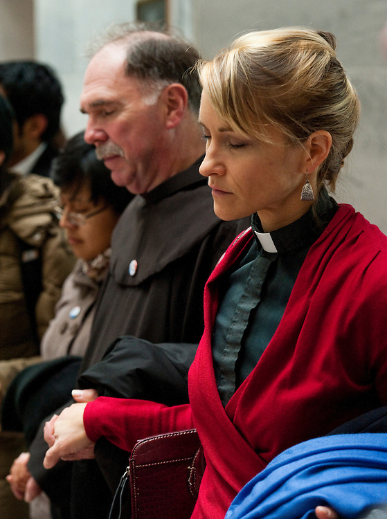 "WASHINGTON, DC- Dec. 14: Rev. Yvette Schock, national grants coordinator for immigration reform for Church World Service, and other participants in a ""Jericho March"" and rally in support of the DREAM Act pray in the atrium of the Hart Senate Office Building. The event was sponsored by Faith in Public Life. (Photo by Scott J. Ferrell/Congressional Quarterly)"
