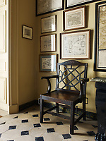 Antique maps of Cuba hang in the entry hall; a sturdy wooden chair sits on the tiled floor.