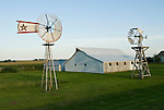 Farm with white barn and historical wooden windmills on the Great Plains of Nebraska