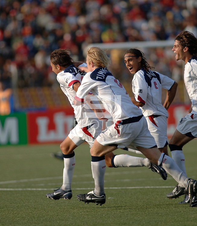 Midfielder Kyle Nakazawa is chased down by teammates Preston Zimmerman, Kevin Alston and Blake Wagner after scoring against Italy. The United States beat Italy 3-1 in the 2005 FIFA World Championship tournament in Peru, September 20, 2005.