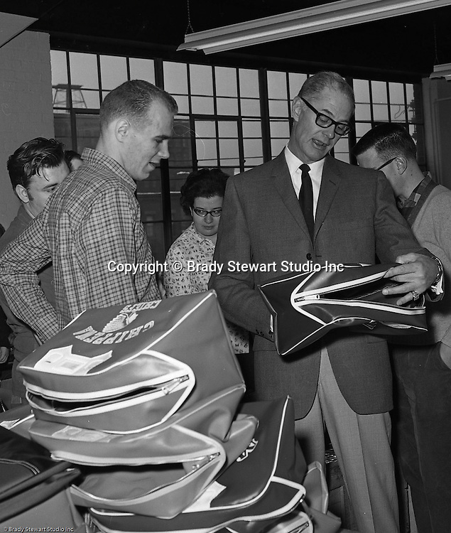 Pittsburgh PA:  Bob Prince touring the Goodwill Industries facility and talking with a few of the workers making gym bags for school districts - 1966.  <br />