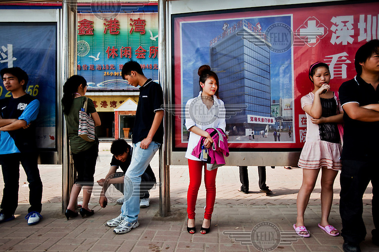 Employees wait a t a bus stop near the Foxconn factory. Foxconn is a Taiwanese technology company that makes products for Apple and Sony among others and is the largest private sector employer in China.