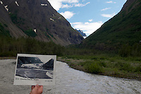 Photographer and geologist Ron Karpilo holding a photograph of Eklutna Glacier taken by U.S. Geogical Survey geologist Stephen Reid Capps in 1915 while repeating the photo on July 31, 2010.  The photo was taken near the Serenity Falls Public Use Hut, Eklutna Lake Area, Chugach State Park, Alaska, United States.