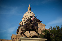 Texas Ranger Cowboy statue stands guard in front of the Texas State Capitol Building.