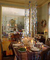 A festive striped cloth covers the dining table which is laid with decorations inspired by frost and ice
