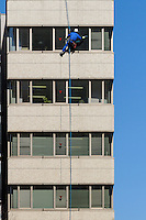 A window cleaner abseiling on a building in Shibuya, Tokyo, Japan. Friday February 17th 2017