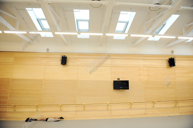 A dancer stretched to warm up for a reheasal in one of the new rehearsal rooms of the newly restored historical Bolshoi theatre. Moscow, Russia, October 19, 2011