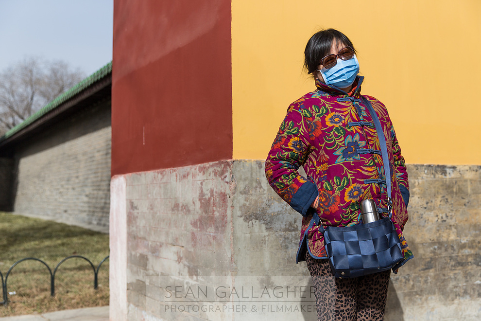A woman stands near a colourful wall in Beijing's TianTan Park. PM2.5 reading - 78 - Moderate