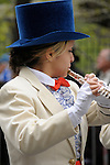 Greek Parade in New York City. A girl in a white coat and a blue top hat plays the flute in the Greek Parade in New York City.