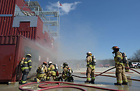 NWA Democrat-Gazette/ANDY SHUPE<br /> Fire captains, firefighters and training officers prepare to enter with a charged line Wednesday, March 7, 2018, during a training workshop for fire department leadership to meet current National Fire Protection Association standards at the Fayetteville Fire Department training facility in south Fayetteville. Thirty students and instructors from agencies in seven states attended the training meant to train department training officers at current standards.