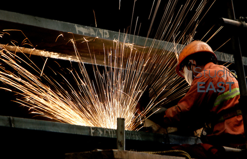 A worker grinds the lift 1 'WSD1 Skin E' of the tower of Self-Anchored Suspension (SAS) bridge in the workshops of Shanghai Zhenhua Port Machinery Co. Ltd. (ZPMC), on Changxing Island, Shanghai, on January 12, 2009. Photo by Lucas Schifres/Pictobank