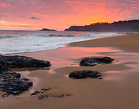 "Kauai, Hawaii: Surf patterns and reflections on Kauapea ""Secret"" beach at sunrise, with Kilauea Point Lighthouse on the distant point"