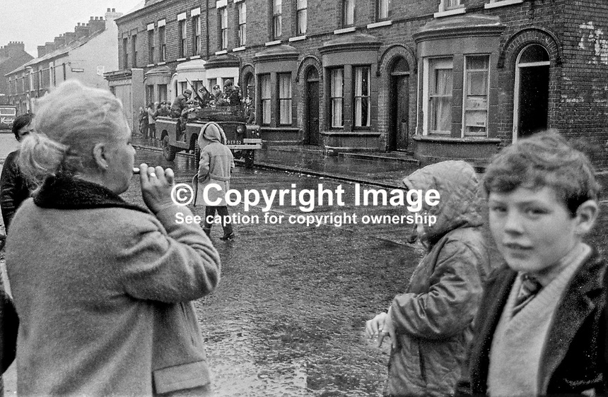 A woman blows a whistle to warn of the presence of a British Army patrol in the Lower Falls area of Belfast, N Ireland. Date uncertain but most likely November 1971. 19711100450f.<br />