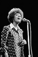 "27 Oct 1972 --- Dionne Warwick giving support during a Women-Only concert to Senator George McGovern of South Dakota, the Democratic candidate for the presidential campaign against Richard Nixon. The ""Musical Spectacular"" at Madison Square Garden also showcased the talents of Tina Turner, Melina Mercouri, Mary Travers, Shirley McLaine, Judy Collins, Bette Davis, with the support of Rose Kennedy. --- Image by © JP Laffont"