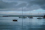 Rowboat with two people passing moored sailboats at dusk, Lunenburg, Nova Scotia, Canada