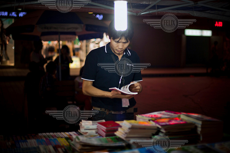 A young man browses books and magazines for sale at a roadside store.
