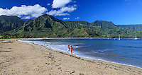 Two women walk along the shore at Hanalei Beach on Kaua'i, with Hanalei Bay to the right.
