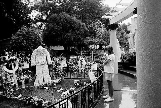 "Memphis, Tennessee <br /> August 14, 2002<br /> <br /> A young girl clings to her teddy bear at the grave of Elvis Presley in Graceland during ""Elvis Week"" marking the 25th anniversary of the King's death."