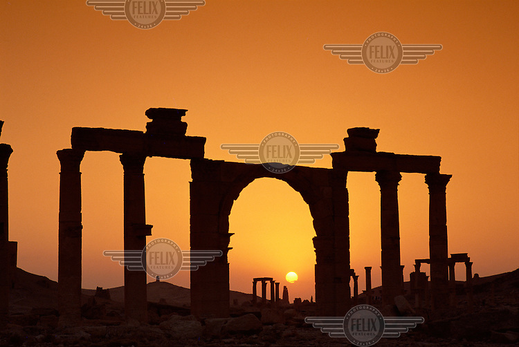 The Roman-era ruins of Palmyra silhouetted against the setting sun.
