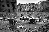 Grozny, Chechyna.1995.A man sits by a fire eating in a destroyed courtyard in the city center.