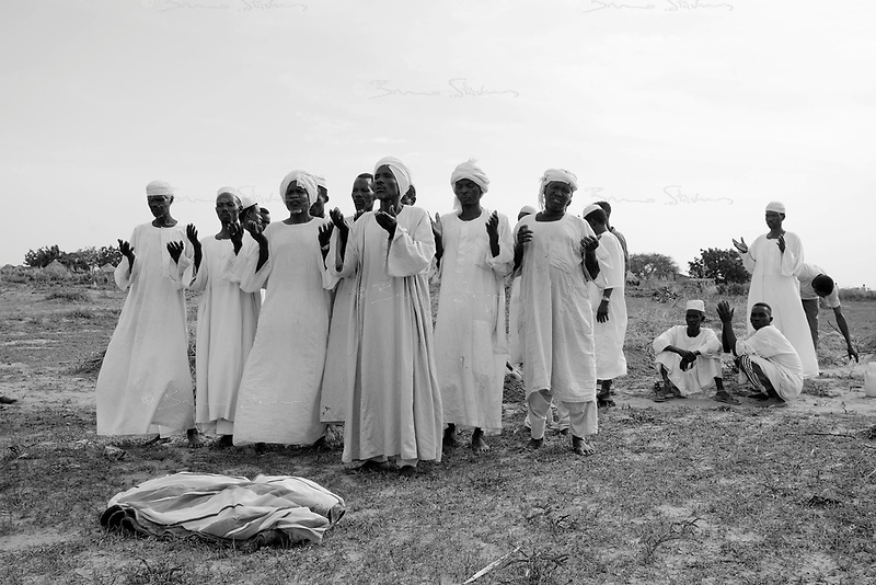 Kalma IDP camp, South Darfur, July 29 2004.Men pray over the body of Abacar Abdallah, 25 months old, before his burial after he died from severe malnutrition, weighing at only 5.2kg, despite desperate last minute efforts by MSF medical staff to save him.
