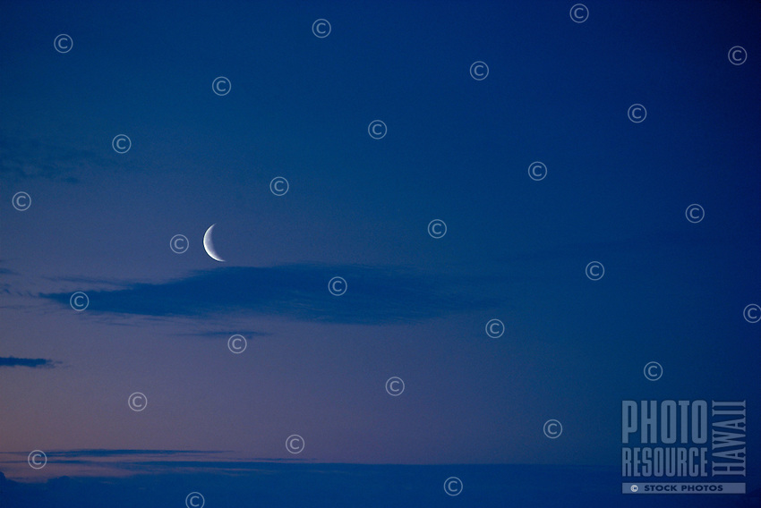 Crescent moon in pale blue sky