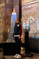 U.S. women national team midfielder Carli Lloyd poses for a photo next to a model of the Empire State Building lit in the Red White and Blue colors of the US Soccer Federation during the centennial celebration of U. S. Soccer in New York, NY, on April 05, 2013.