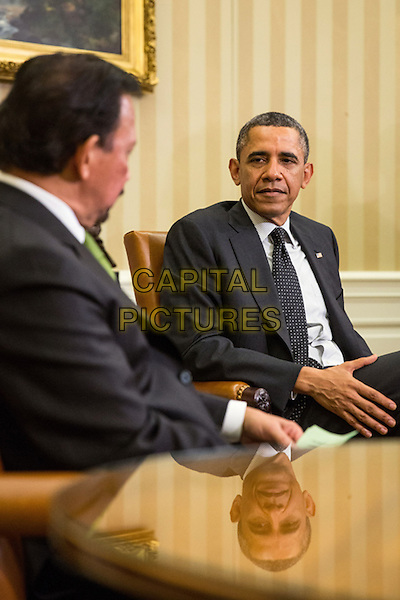 United States President Barack Obama (R) sits with Sultan Haji Hassanal Bolkiah of Brunei, at the end of a bilateral meeting in the Oval Office at the White House on March 12, 2013 in Washington, DC. The two discussed strategic and economic issues in advance of October's East Asia summit and US-ASEAN summit in Brunei.  .half length suit black white stripe shirt side profile .CAP/ADM/CNP/DA.©Drew Angerer/CNP/AdMedia/Capital Pictures.