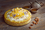 Healthy home-made flourless, sugar-free, dairy-free vegan cake made of almond flour, oranges and coconut, artistic food still life with a clay teapot on rustic wooden table background Image © MaximImages, License at https://www.maximimages.com