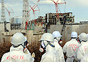 February 20, 2012, Fukushima, Japan - Members of the media, TEPCO, and the Nuclear and Industrial Safety Agency (NISA), wearing protective suits and masks, look at the tsunami-damaged Fukushima No. 1 Nuclear Power Plant's, from left to right, No. 1, 2, 3 and 4 reactor buildings on Feb. 20, 2012 in Okuma, Fukushima Prefecture.
