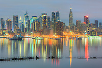 The Manhattan skyline during morning twilight as viewed over the Hudson River from New Jersey.  The motionless river contributed a mirror-like reflection of the skyline.
