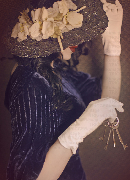 A brunette young adult female dressed in period vintage clothing wearing white gloves with her face hidden, holding a set of vintage keys