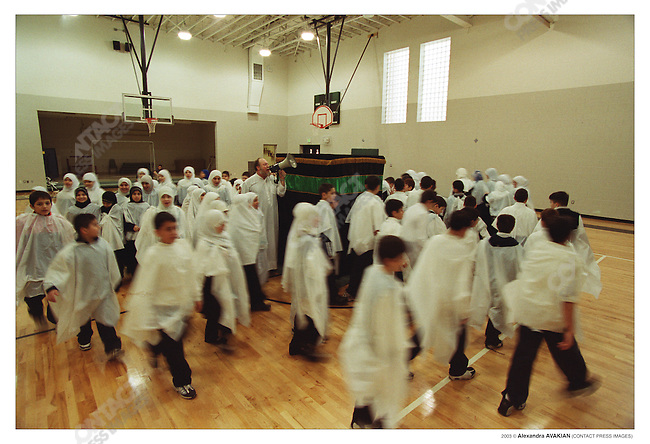Lebaneses-American students circle a model of the Ka'aba built in the center of the gym, practicing the pilgrimage to Mecca, a Shi'ia school, Michigan, February 2002
