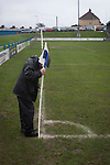 A club official putting a corner flag into the pitch before Port Talbot Town played host to Caerau Ely in a Welsh Cup fourth round tie at the Genquip Stadium, formerly known as Victoria Road. Formed by exiled Scots in 1901 as Port Talbot Athletic, they competed in local and regional football before being promoted to the League of Wales  in 2000 and changing their name to the current version a year later. Town won this tie 3-0 against their opponents from the Welsh League, one level below the welsh Premier League where Port Talbot competed, watched by a crowd of 113.