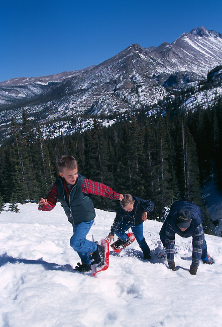 A father and two sons having fun while snowshoeing in the Rocky Mountains of Colorado