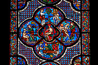 Medieval stained glass Window of the Gothic Cathedral of Chartres, France - dedicated to the lGood Samaritan . Central panel shows Adam dwelling in Paradise, below - At the inn, the Samaritan nurses the injured man back to health, left - God breathing life into Adam, above - God warning Adam and Eve not to eat from the tree of knowledge, right - God creates Eve out of Adam's rib .  A UNESCO World Heritage Site..