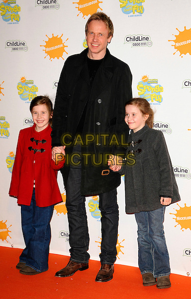 """TIM LOVEJOY & GUESTS.At the """"Spongebob Squarepants - The Sponge who could Fly"""" Gala performance at the Hammersmith Apollo, London, England. .March 5th 2009 .full length jeans denim black red grey gray jacket coats kids children holding hands .CAP/CAN.©Can Nguyen/Capital Pictures."""