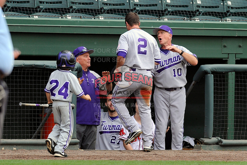 Outfielder Will Muzika (2) of the Furman Paladins is congratulated at home plate by head coach Ron Smith (10) after scoring on a base hit in a game against the Elon Phoenix in the first round of the Southern Conference Tournament game on Wednesday, May 22, 2013, at Fluor Field at the West End in Greenville, South Carolina. Furman won, 10-1. (Tom Priddy/Four Seam Images)