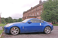 A blue Nissan 350Z Japanese sportscar in front of an old British mansion.