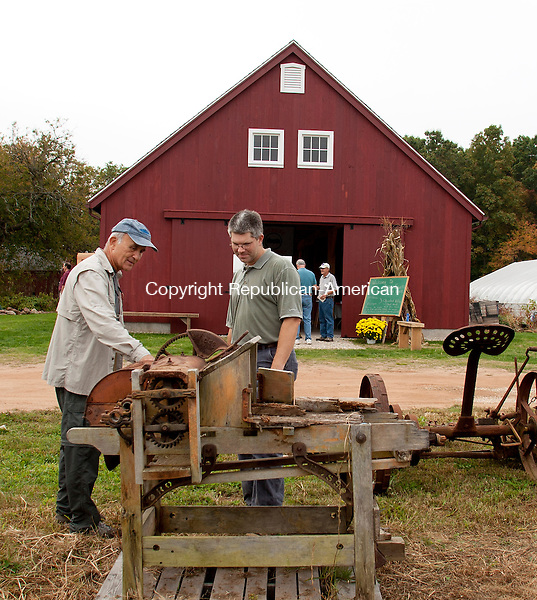 "CHESHIRE, CT-5 October 2013-100513BF02-  Members of the Cheshire Land Trust Dave Schrumm from Cheshire, left, and Mark Kasinskas look over some of the old farm equipment on display during the Cheshire Land Trust's ""A Day at the Farm"" event at Ives Farm on Cheshire Road in Cheshire Saturday. The Cheshire Land Trust acquired the 164-acre Ives Farm in 2006.  Bob Falcetti Republican-American"