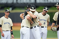 Wake Forest Demon Deacons relief pitcher John McCarren (45) gets a hug from teammate Carter Bach (18) as he is taken out of the game against the Pitt Panthers at David F. Couch Ballpark on May 20, 2017 in Winston-Salem, North Carolina. The Demon Deacons defeated the Panthers 14-4.  (Brian Westerholt/Four Seam Images)