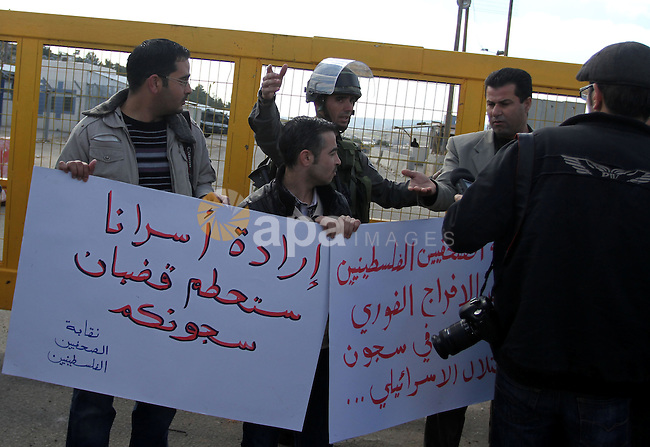 Palestinian journalists carry placards during a protest in support of jailed journalists and prisoners on hunger strike in Israeli prisons, in front of Ofer military prison, near the West Bank city of Ramallah, on February 20, 2013. Some 800 Palestinians serving time in Israeli jails were refusing food in solidarity with four fellow inmates who have been on long-term hunger strike, officials said. Photo by Issam Rimawi