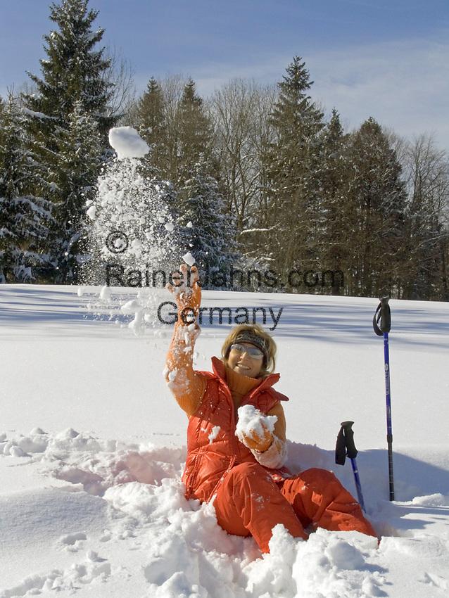 Deutschland, Frau beim Nordic Walking im Winter, im Schnee sitzend, wirft Schneeball | Germany, woman doing nordic walking in winter, sitting in the snow, throwing snowball