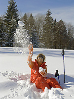 Deutschland, Frau beim Nordic Walking im Winter, im Schnee sitzend, wirft Schneeball | Germany, woman doing nordic walking in winter, sitting in the snow, throwing snowball