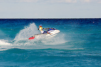 Smiling man on jet ski waving as he splashes through waves
